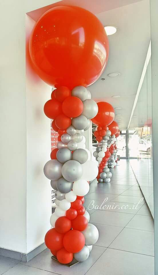 Bright balloon columns in orange, white and silver.