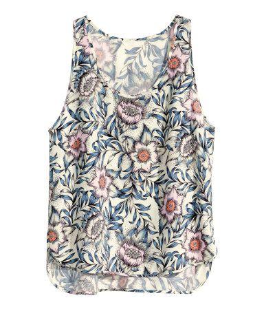 Blusa de tela sin mangas con estampado, aberturas en los laterales y parte trasera más larga.
