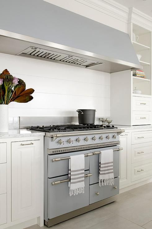 A long, gray kitchen hood stands over a shiplap backsplash and a white French stove, Lacanche Chagny Cooking Range flanked by open shelving.