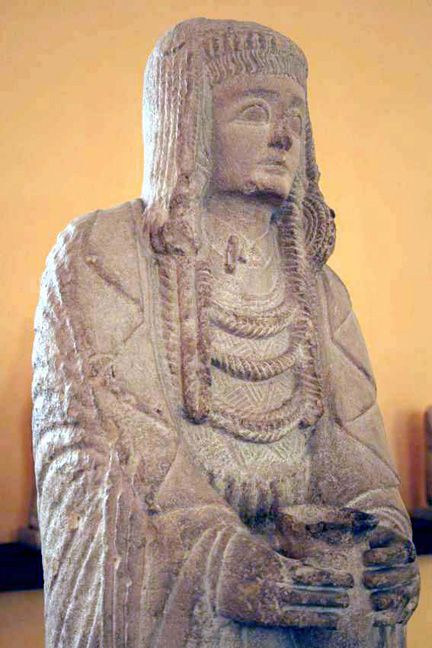La Gran Dama Oferente  del Cerro de los Santos. A classic of Iberian sculpture, she stands four feet high, holding a libation cup over her womb. She wears rich robes, necklaces, and a headdress with a rodete pendant like that of the Dama de Elche.    Limestone, 1.3 meters (51 inches).  Montealegre del Castillo, Albacete. 400-100 BCE.