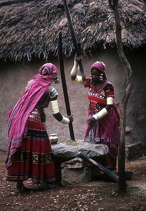 INDIA: Two woman in pink sarees grinding grains. Banjara, Andhra Pradesh