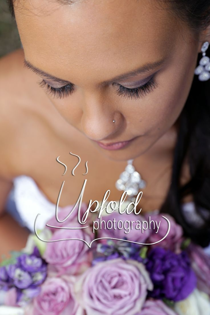 A very beautiful, serene bride, showing her immaculate makeup and gorgeous bouquet in shades of purple. Image by Upfold Photography, Auckland.