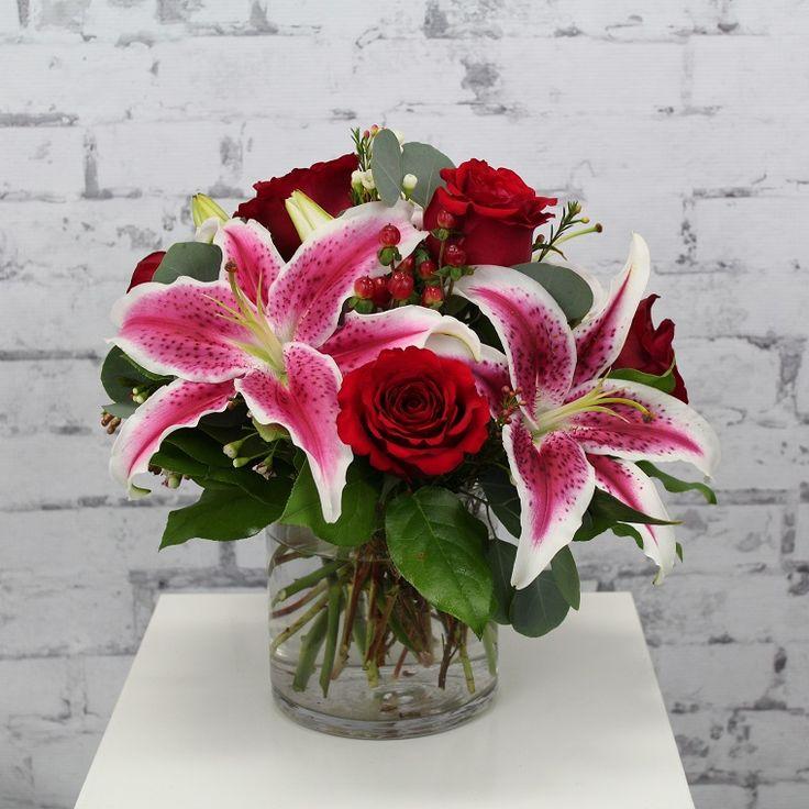 composizioni floreali: un vaso trasparente con rose rosse e lillium