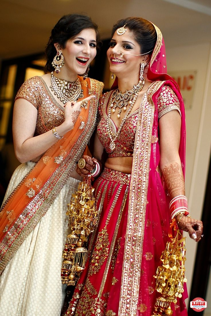 Sister of the Bride - Bride in a Red Lehenga with Scattered Sequin Work and the Sister in a Light White and Orange Lehenga  #wedmegood #sisterofthebride #indianwedding #indianbride #lehenga #red