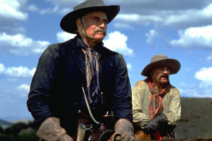 Two veteran actors famous for their westerns that were intended to show up in Tombstone were Glen Ford and Robert Mitchum.  Ford pulled out for some reason and was replaced with Harry Carey Jr. Mitchum (cast as the patriarch of the Clantons) was injured in a horse riding accident early in the filming. Mitchum's lines were given to to Powers Booth and other actors and Robert Mitchum ended up the narrator of the film.  Charlton Heston appeared as planned as rancher Henry Hooker.