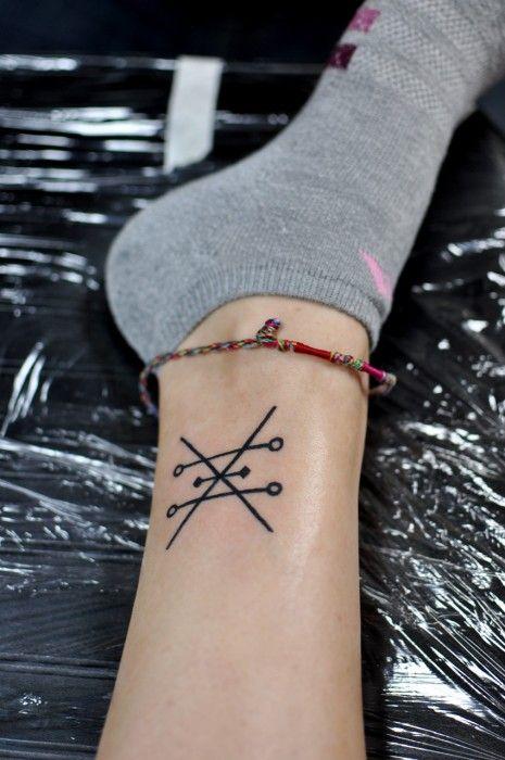 Chica con un tatuaje de alquimia en su pie. Este símbolo del cobre significa amor, equilibrio, belleza femenina y creatividad artística.
