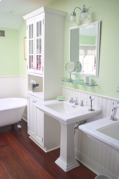 the white cabinetry sinks tile and wainscot paneling create a bold contrast against red oak
