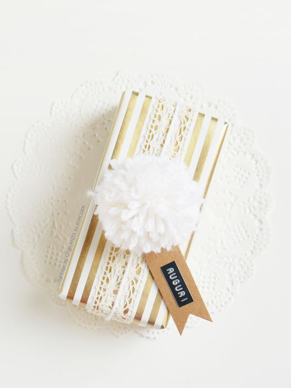 White pompom and golden wrapping paper.