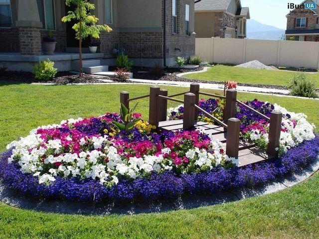 Цветы на клумбах могут быть разными, главное их сочетание. На этой клумбе наибольшее количество петуний. Они разных цветов и делают гармоничное сочетание в дизайне. Деревянный мостик красиво дополн...