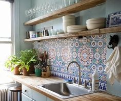 Cuisine : meubles blancs, plan de travail et étagères en bois, crédence en carreaux de ciment