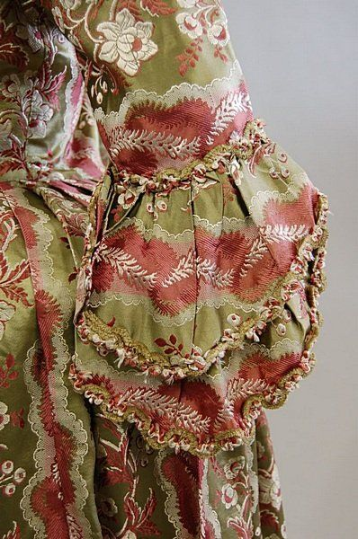 Detail sleeve, robe à l'Anglaise, fabric late 1760s-early 1770s. Green brocaded silk satin, the sage green ground woven with pink and ivory feathery bands and blooms, chenille braid to the engageants and front robings.
