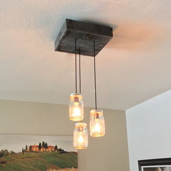 Handcrafted rustic industrial pendant light that can go with any decor in your home. It has three mason jar pendants, retro sockets and reclaimed pallet wood with a beautiful patina. Price Includes: - Wood canopy - 3 mason jar fixtures - 2 hanging eye bolts - 2 feet of extra wire if you dont wish to flush mount it to ceiling. * Edison light bulbs are not included but can be bought at a hardware store near you. Approximate Canopy Dimensions: 13.5 x 12.5 x 3 Bottom of longest pendant is a...