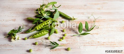 green pea pod, fresh green peas, peas flowers and leaves on wooden background, flat lay, top view