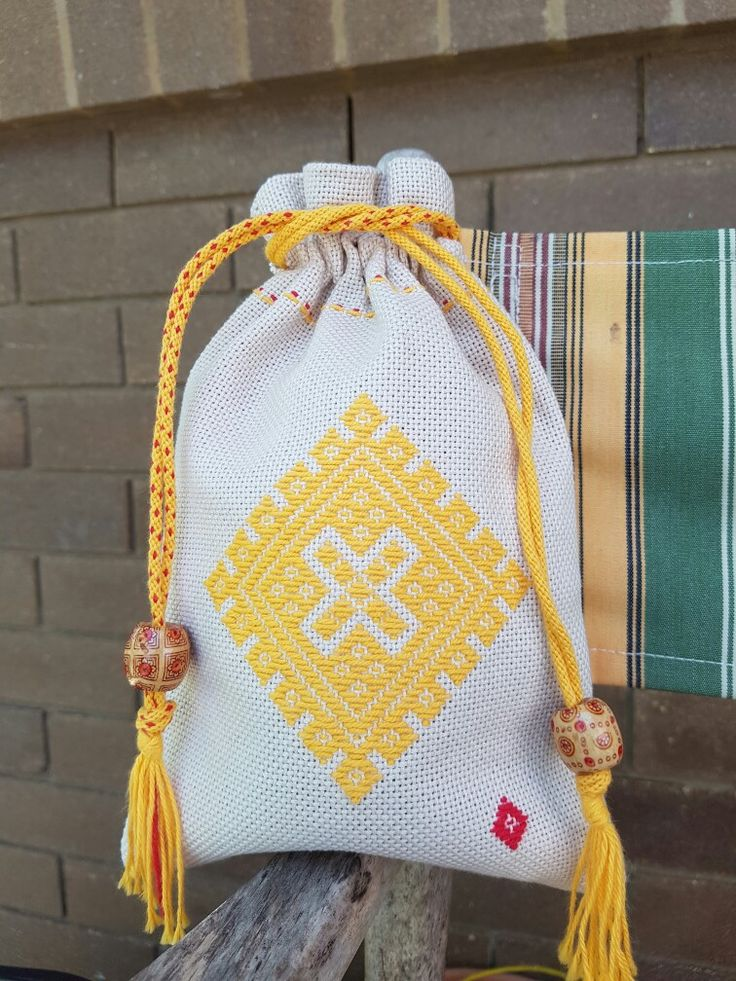 Kogin embroidered pouch with kumihimo drawstring finished with wooden beads.