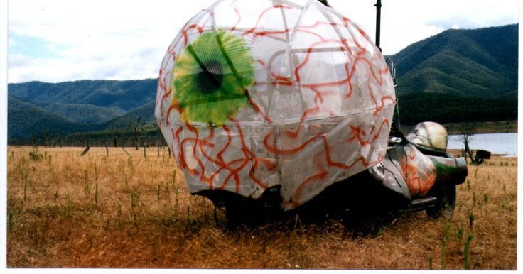 All Seeing Eye  2000 Dimentsions 2m(h) x2m(w) x 4m(l) Materials modified Datson 1600 in Sculptural form. washing machines, 44 gallon drums, 12volt projectors, sound installation Location Earthcore NYE Y2K Lake Eildon National Park, Victoria. Photo Paul Irving