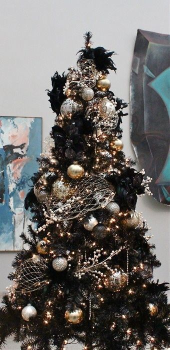 a black Christmas tree decorated in gold and silver for a chic gothic inspired look