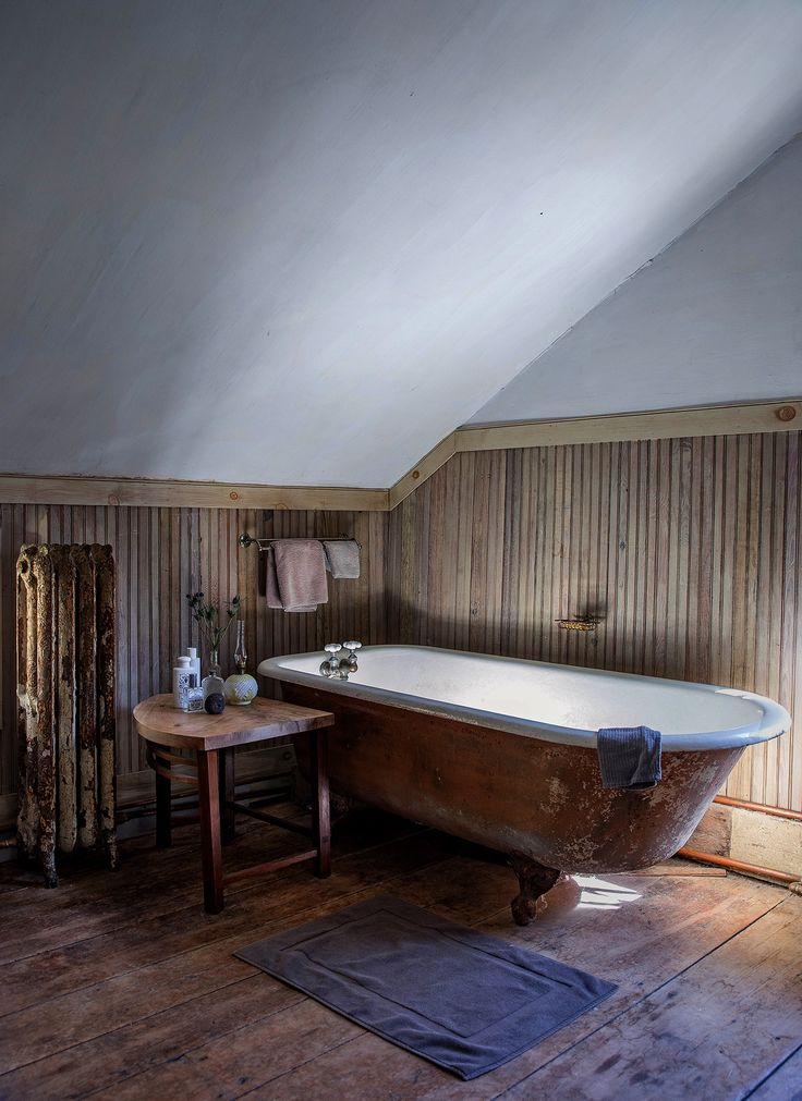 Don and Ray devoted one corner of their bedroom as the master bath. Here, an antique claw-foot tub illuminates the beadboard wainscoting and plaster ceiling.