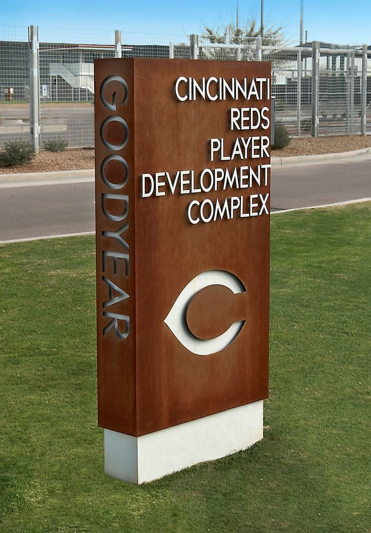 A freestanding monument constructed of water jet cut Cor-Ten steel and brushed aluminum flat cutout letters helps direct players to the Reds development complex.