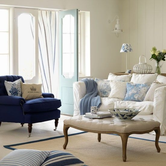 This elegant decorating idea blends relaxed modern living - in the form of a slouchy sofa - with a more traditional style ottoman and deep armchair.