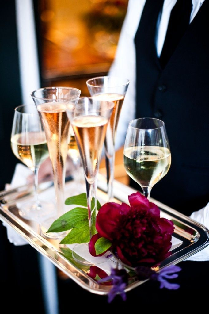 The waiter serves more wine but this time someone has placed a rose on his tray. Who could it be for?
