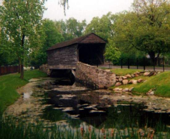 (Ackley or Greenfield Covered Bridge, 75', 1832, Burr variation, 22-82-01) across a Lagoon in Greenfield Village in the Henry Ford Museum in Dearborn, Wayne County, Michigan. MI12 (Michigan Av.) W. 1.4 miles from jct with MI39 (Southfield Fwy), S. on Oakwood Blvd 0.6 miles to the entrance of the park. Admission. (1-28-05, N42° 18.25', W83° 13.46') Photo by Bill Eichelberger.