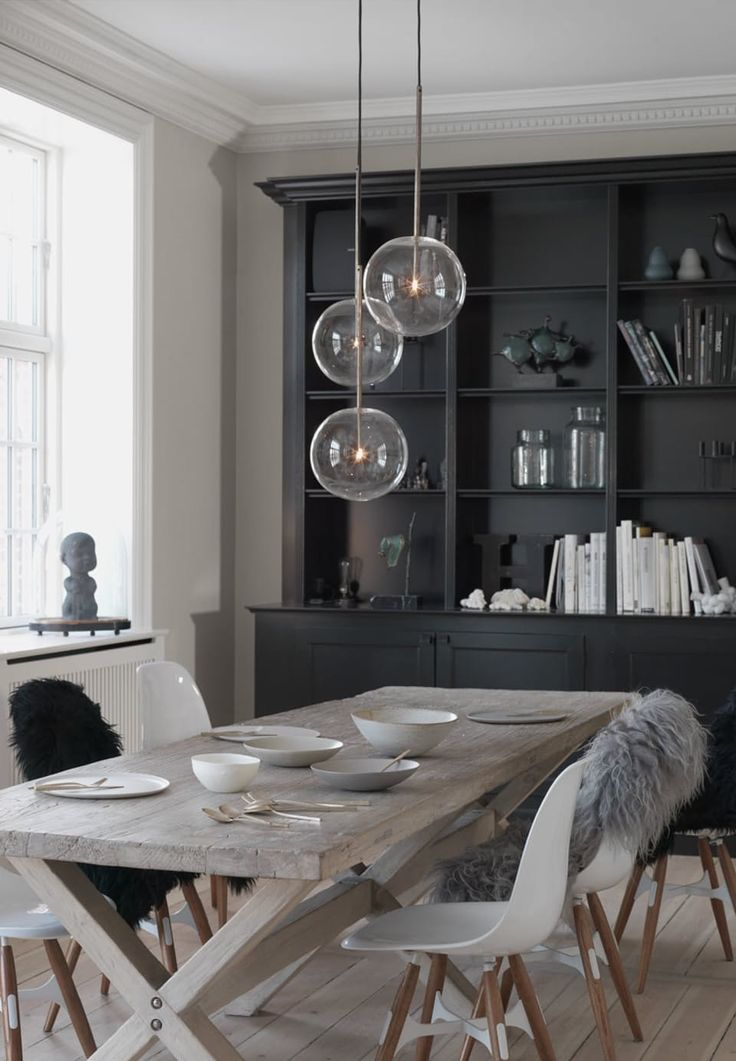 Scandinavian dining room space in neutral tones featuring a rustic plank table and glass pendants.