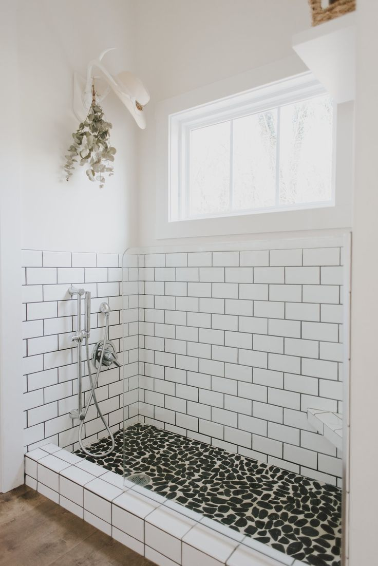 Subway tile. Modern farmhouse. Dog shower. Mudroom. Boot wash. Pebble tile. Rock. White walls.
