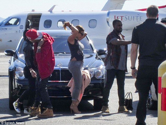 Taking care of business: Kim Kardashian was seen tying back her hair as Kanye West took care of business as they arrived in Las Vegas alongside her friends including Blac Chyna and Tyga