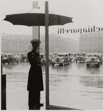 """""""Chez Schiaparelli"""", homme en costume avec un parapluie, place Vendôme. Paris (Ier arr.), 1937. Photographie de Roger Schall (1904-1995). Paris, musée Carnavalet."""