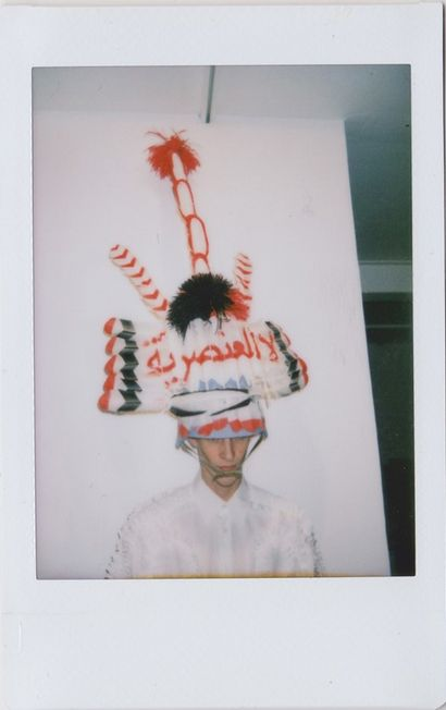 Male Model Backstage in Headdress at Walter Van Beirendonck.Fashion Week Polaroid PIctures by Dazed & Confused Magazine.