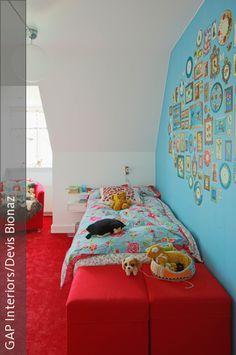 Ein Mädchenzimmer muss nicht immer pinkfarben sein. Dieses Zimmer ist ein perfektes Beispiel dafür, dass ein Mädchenzimmer auch durchaus andere Farben haben darf. Eine blau gestrichene Wand mit aufgeklebten Bilderrahmen ist kreativ und bietet Platz für eigene Fotografien und Bilder. Roter Teppich und Möbelstücke in Rot bilden einen gewagten Kontrast zu dem Blau und dennoch schaffen sie ein angenehmes Ambiente. Bettwäsche und Kissenbezüge im floralen Design bringen einen zarten…