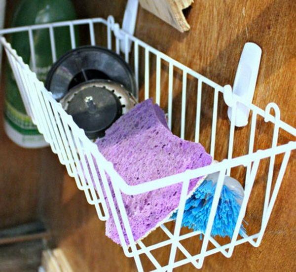 Hang a simple dollar store basket on the inside of your cabinet door. It's a clever under sink storage idea for wet sponges and brushes and give them air to dry. http://hative.com/creative-under-sink-storage-ideas/