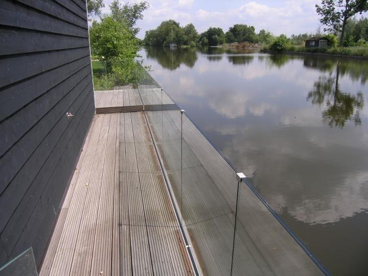 Glazen balustrade langs terras aan het water.