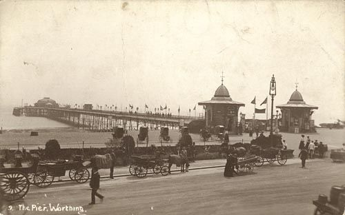 Worthing Pier, designed by James Mansergh in the 1880s, looking south west. View of the pier shows the entrance kiosks (designed by Alfred Crouch) to the pier head. Men, women and children are walking around while horse drawn taxis ply their trade on the street. Bathing machines can be seen on the beach. Worthing West Sussex England