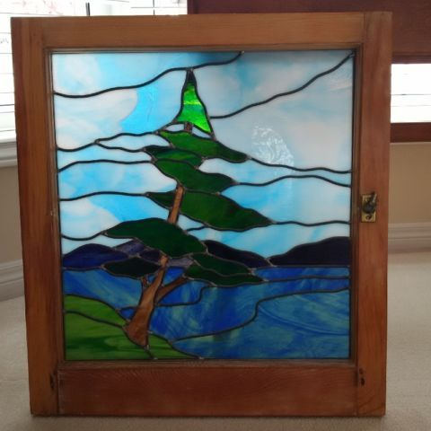 """custom made stained glass in the look of """"the group of seven"""". this leaning pine piece measures 24 """" wide by 26.5"""" high and has been installed in an antique frame - the original brass latch can be seen on the right side of the frame. mounted in a window or simply on a wall, this piece is a beautiful work or art."""
