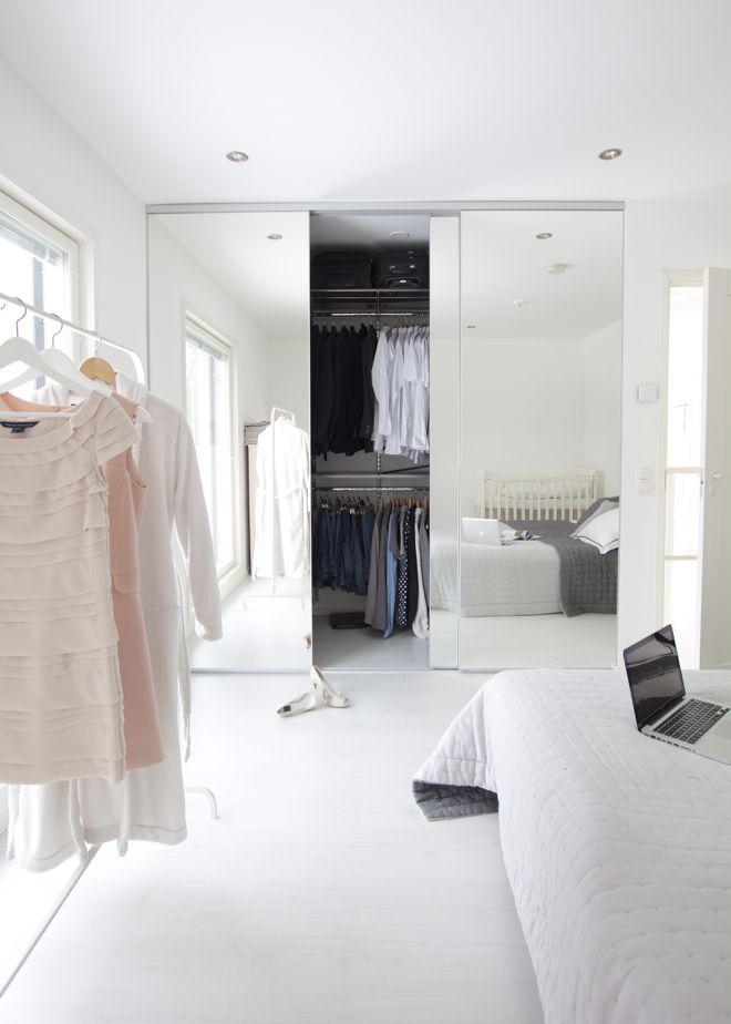 Use of mirrors on the wardrobe doors amplifies light and the feeling of space in this bedroom.