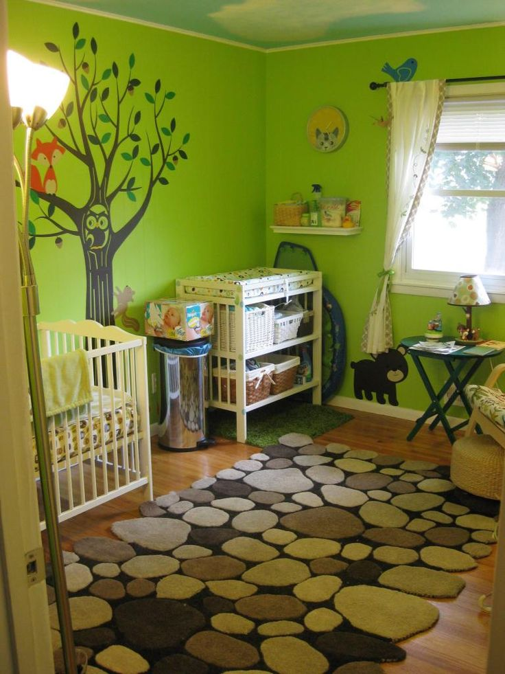 "Forest theme nursery    Paint color: ""Fresh Sprout"" walls (Behr), blue sky and cloud ceiling (various sky blue/white/mauve paints)    Vinyl wall decals: SimpleShapes.com    Rug: Rock rug (Overstock.com)    Crib, changing table, curtains: IKEA    Table lamp: Carters forest friends    Cat clock: Target.com"