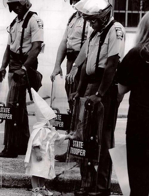 The child of a KKK member touches his reflection in an African American police officer's riot shield during a demonstration. [1992]