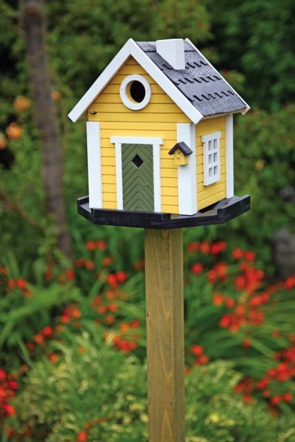 Cheery Yellow Birdhouse in the Garden.  Love that it has it's own tiny little birdhouse decoration!