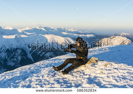 Tourist pours hot tea from a thermos into a cup in the winter in the mountains.