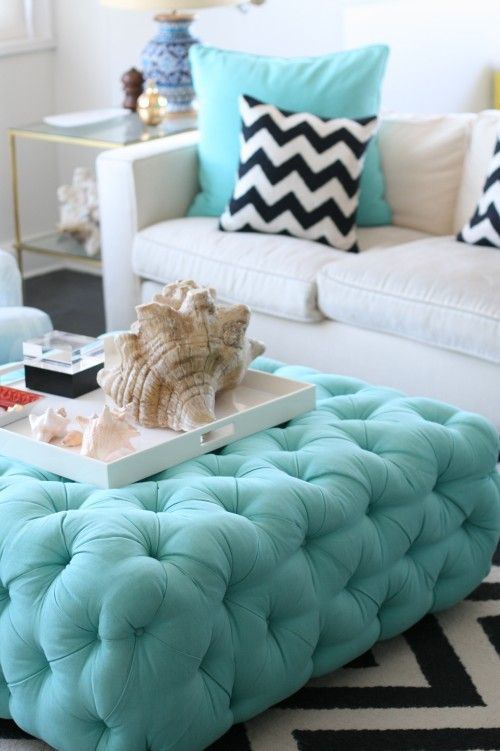 tufted teal ottoman ~ modern white couch with black and white chevron throw pillow and rug ~ tray with seashells ~ cool living room design