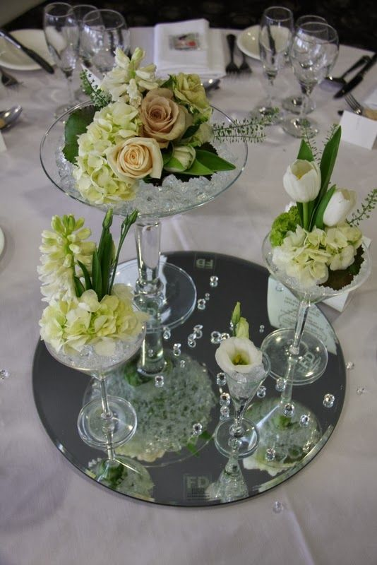 Quite like the mini arrangement in the tall glass to give some height - we could do this instead of having them flat.