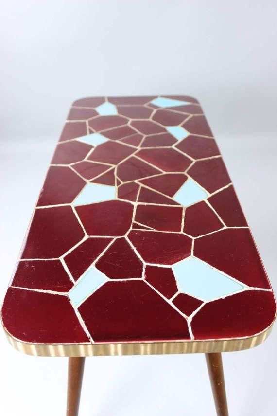 Vintage Mosaiktisch, Beistelltisch, Blumentisch, Coffeetable | 50er 60er Jahre  Ein wunderbarer Mosaiktisch aus der Mid Century Zeit. Die Tischplatte ist aus Holz, sie hat eine stabile Metallleiste und die Tischfläche besteht aus echten Mosaiksteinen. Das Mosaik hat eine ganz tolle Farbkombination aus dunkelroten Kacheln, die mit hellblauen Fliesen aufgehübscht werden. Der Tisch steht auf 4 Holzfüßen, die am Fußende noch die klassische Metallkappe haben.  Ein echter Hingucker für den…