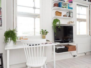 Telewizor i białe półki na metalowych stelażach wiszące na ścianie między oknami,białe biurko z białym drewnianym krzesłem przy oknie w salonie,bielona naruralna podłoga z drewna (26263)
