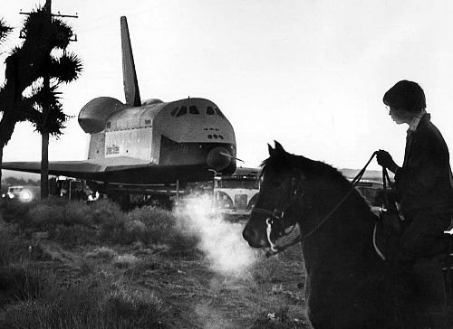 mille:    Jan. 31, 1977: A horse and rider watch as the space shuttle Enterprise is towed from a Rockwell International facility in Palmdale to Edwards Air Force Base for a year of flight tests. Townspeople lined the route for a glimpse of the 110-ton shuttle. A 90-wheel transport was used and accompanied by a 20-vehicle convoy. (via)
