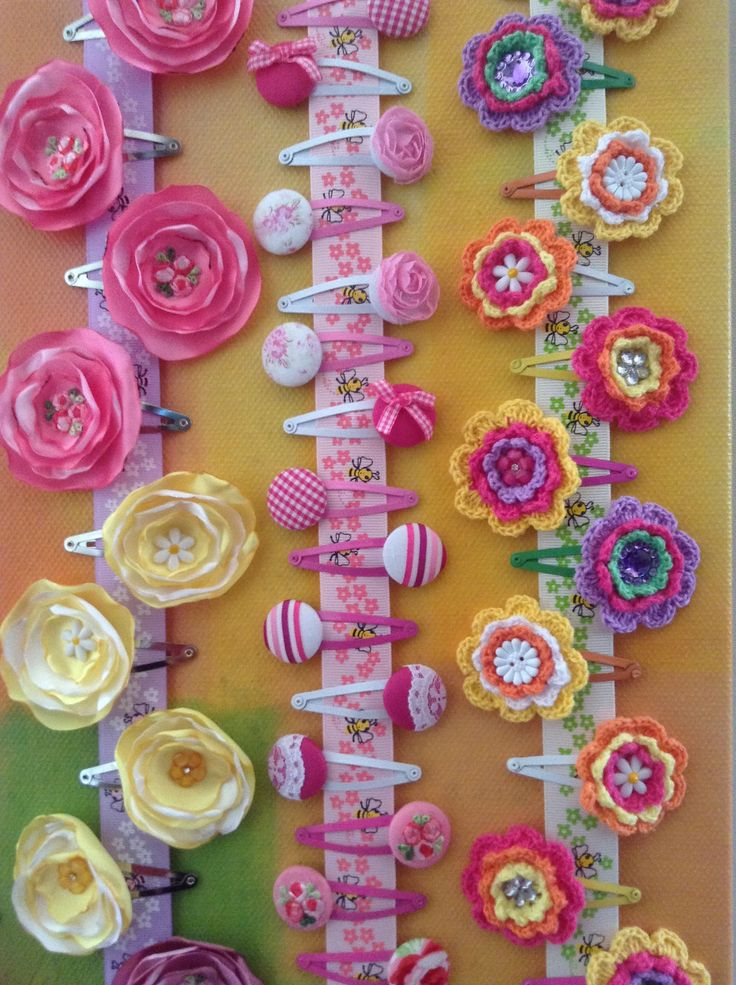 Pretty handmade hair clips displayed on a large canvas for the Arts & Craft stall of the school fete. Features satin flowers (singe the outer edge of different sized satin circles with a match/lighter to create petal look); button hair clips; and crochet flowers (bought flowers off ebay and matched them with coloured snap clips and embellishments).