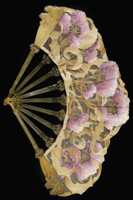 AN ART NOUVEAU HORN FAN, CHARLES HAIRON, PARIS, CIRCA 1910. The slender guards and sticks carved as angelica flowers, the painted silk leaf cut out over net with purple-tinged angelica flowers further embellished with tinted spangles, amethyst-set rivet, signed on guard: C. Hairon. #ArtNouveau #Hairon #fan