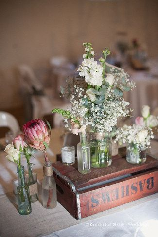 Light and natural flowers in glass bottles and jars; touches of fynbos