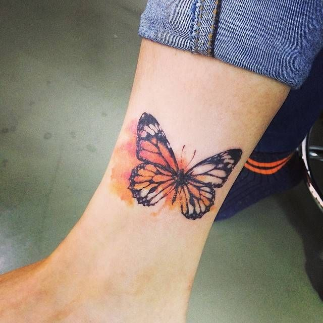 Tatuaje de una mariposa de color naranja situada en el interior del tobillo derecho. Artista tatuador: Doy