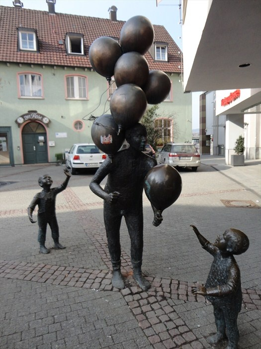 At the pedestrian area 'Bronngasse' in Herrenberg, Germany, Baden-Württemberg, stands a figurative public sculpture called 'Ballonverkäufer' (Balloon Seller).